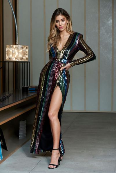 Poses with arm in side in sequin dress with lamp on her right