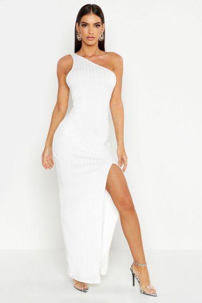 Woman posing in a white dress showing leg