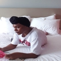black woman with headwrap reading book in hotelroom