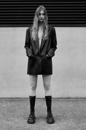 Black and white photo of girl in blazer dress with leather track sole boots